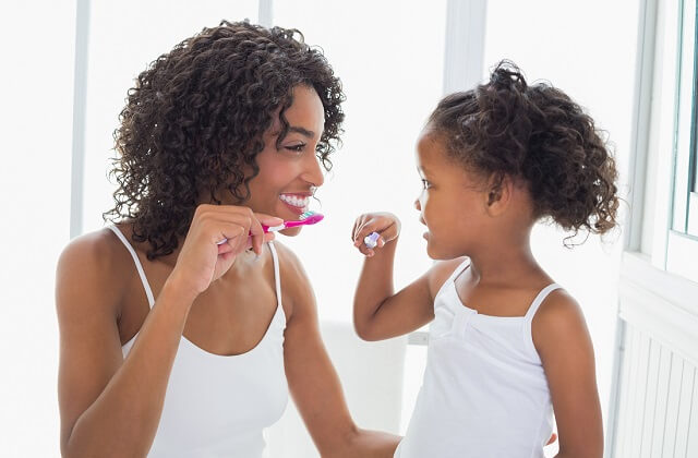Teeth cleaning represented by a mother and daughter cleaning their teeth.